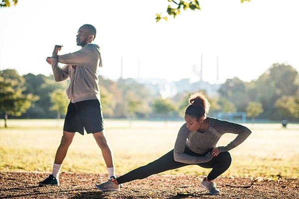 A man and a woman in a field stretching before exercise