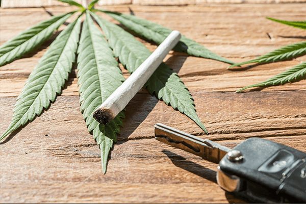 A cannabis leaf lying on a wooden table, with a rolled joint over top, and a set of car keys next to it.