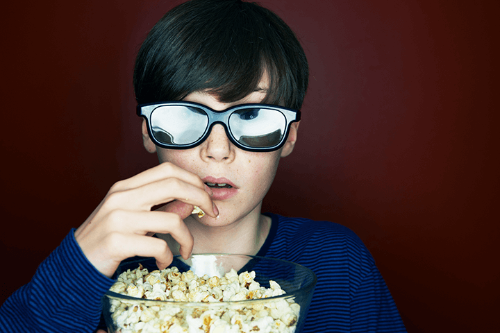 A young boy wearing 3D glasses, eating popcorn with a look of suspense and anticipation