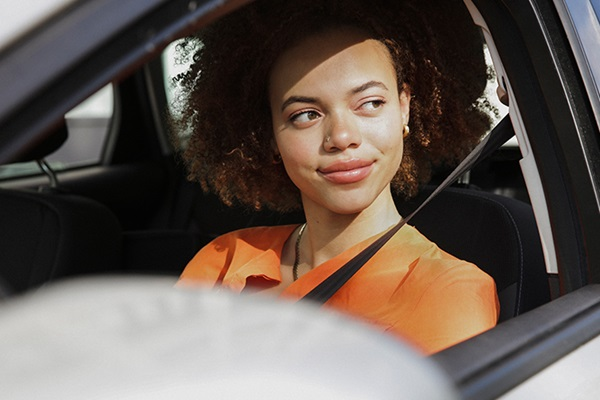 A young woman driving a vehicle, looking out the driver-side window with a thoughtful look and smile on her face.