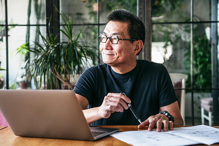 Middle aged Asian man sitting at a desk in front of a lap top, looking out the window and smiling.